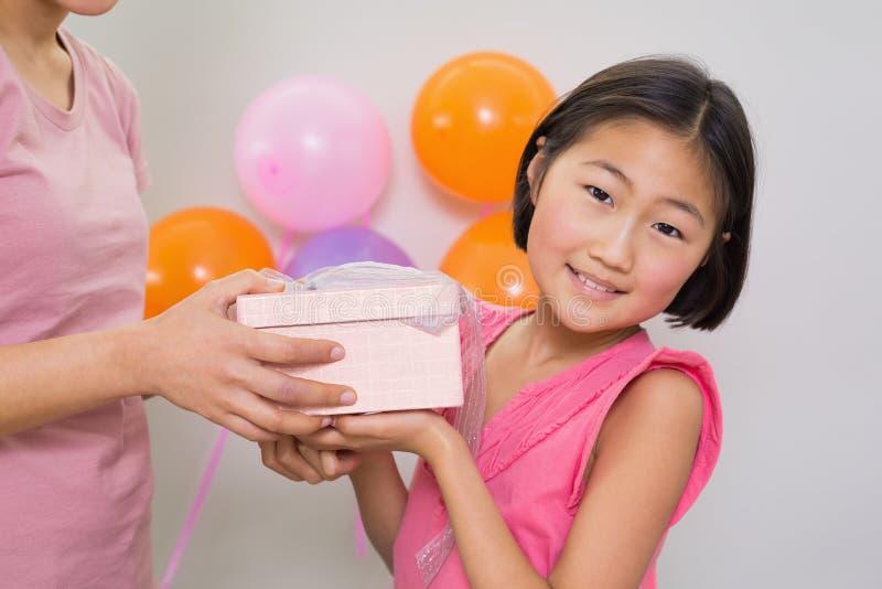 Donna che dà il contenitore di regalo ad una bambina ad una festa di compleanno immagini stock libere da diritti