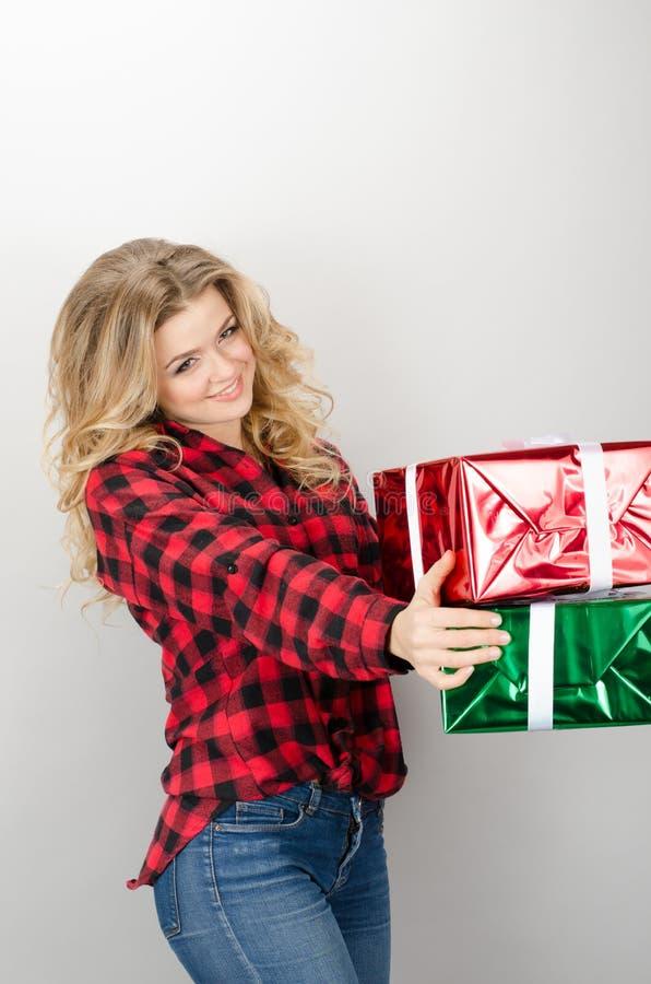 Donna che dà la parte posteriore sorridente di grey dei regali fotografia stock