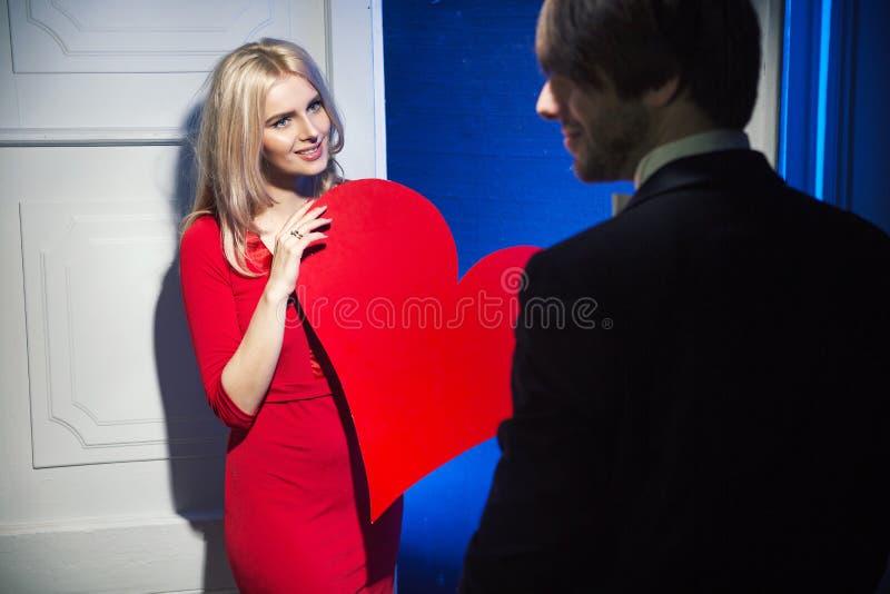 Donna che dà un cuore al suo marito fotografia stock