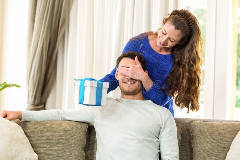 Donna che dà un regalo di sorpresa al suo uomo immagine stock
