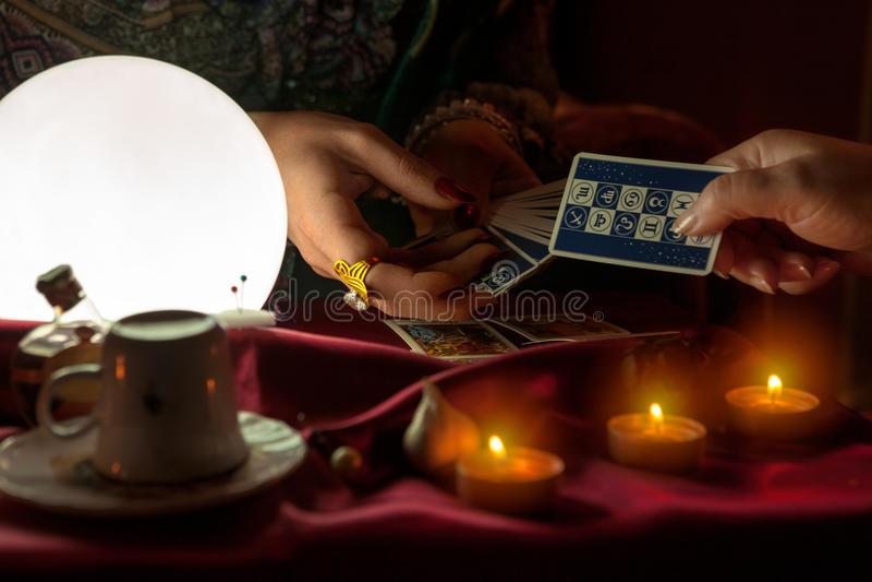Donna che dà una carta di tarocchi alla donna dell'indovino fotografia stock libera da diritti