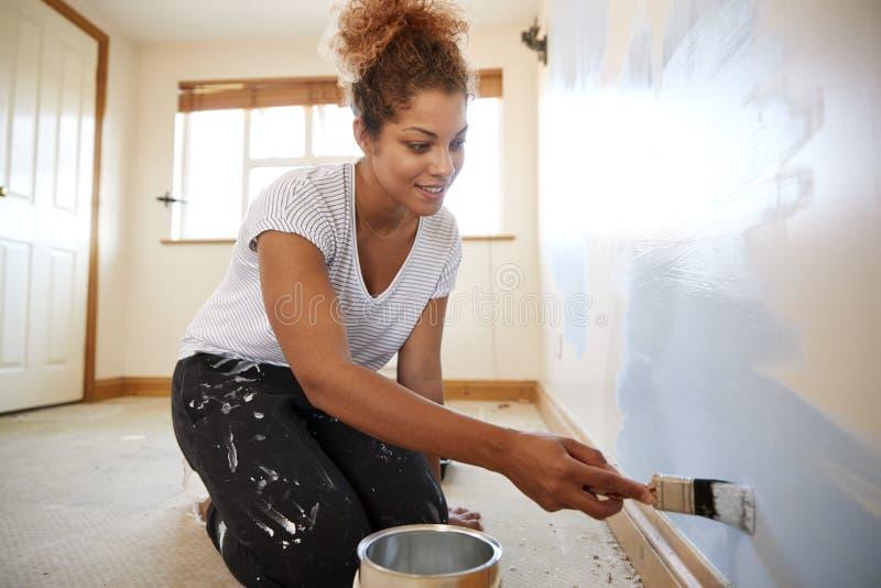 Donna che decora stanza in nuova parete di verniciatura domestica immagini stock