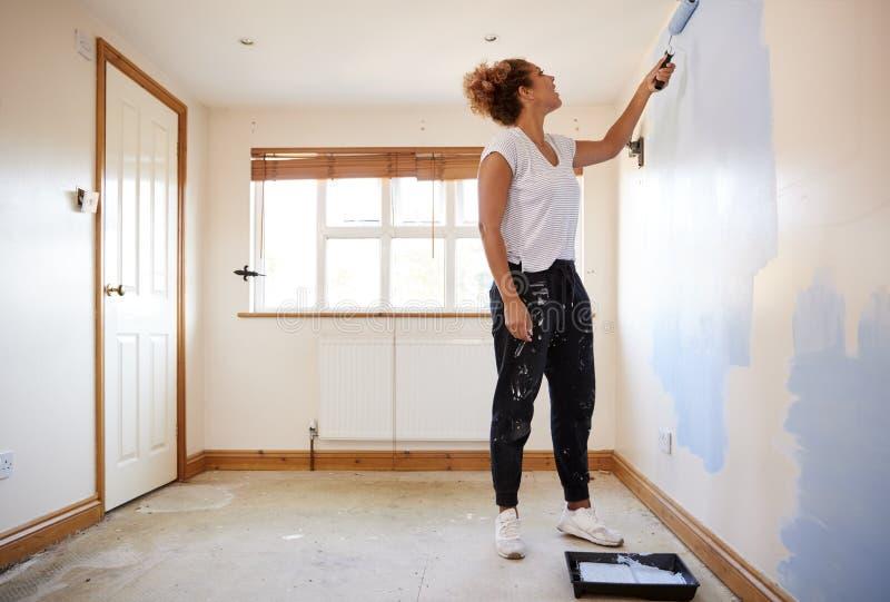 Donna che decora stanza in nuova parete di verniciatura domestica immagine stock