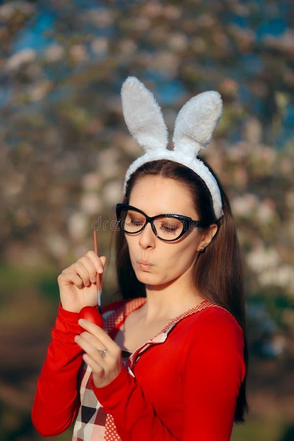 Donna che dipinge le uova rosse tradizionali per la celebrazione di Pasqua fotografia stock