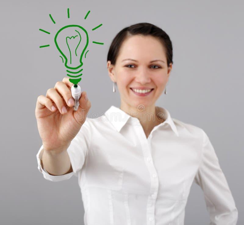 Donna che disegna una lampadina immagini stock