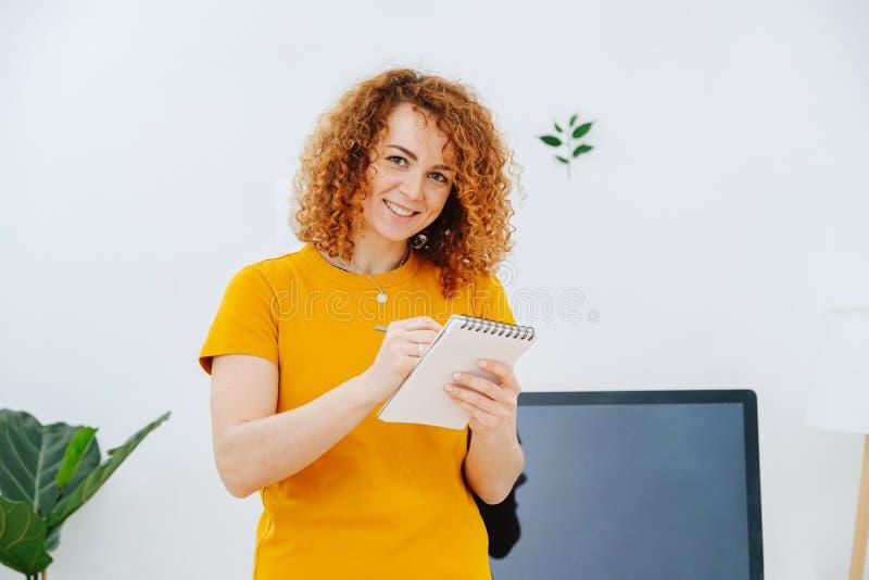 Donna che disegnava un ritratto nel suo taccuino con del crayon, sorridendo alla macchina fotografica fotografia stock libera da diritti