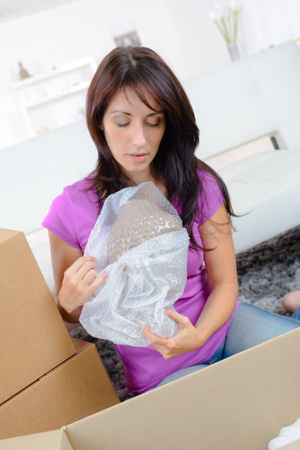 Donna che disimballa il contenitore di cartone con il film protettivo durante muoversi immagine stock libera da diritti