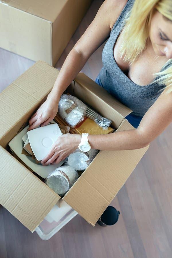 Donna che disimballa le scatole commoventi immagini stock