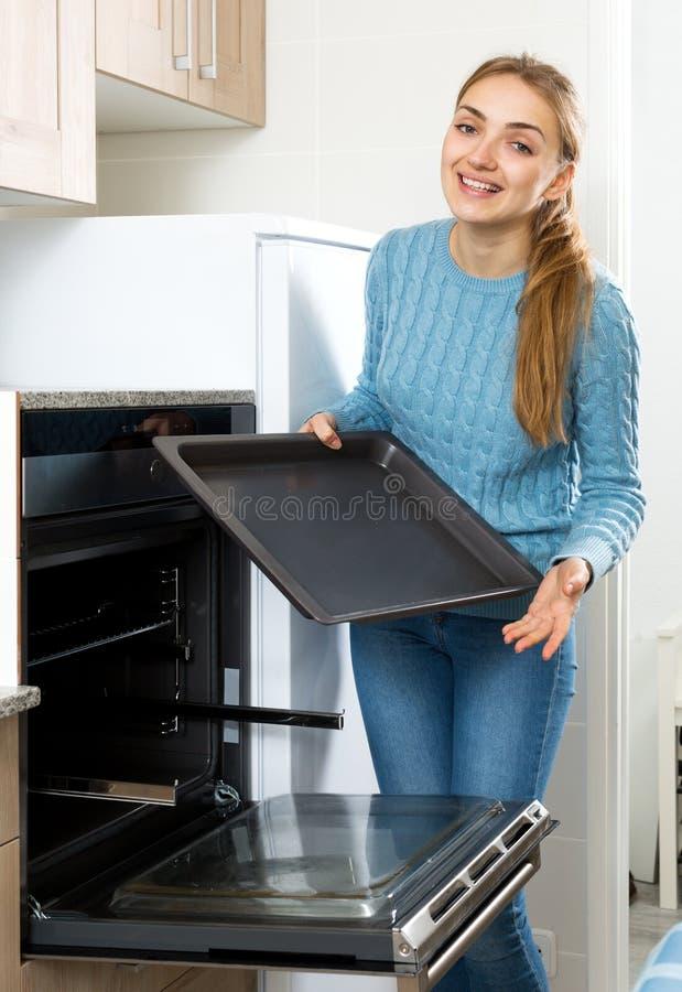 Donna che dispone il vassoio di torrefazione in forno della cucina fotografia stock