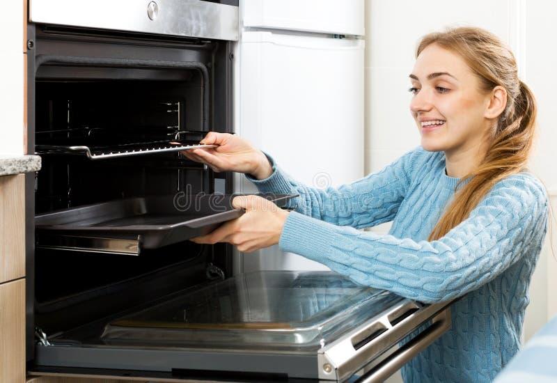 Donna che dispone il vassoio di torrefazione in forno della cucina fotografia stock libera da diritti