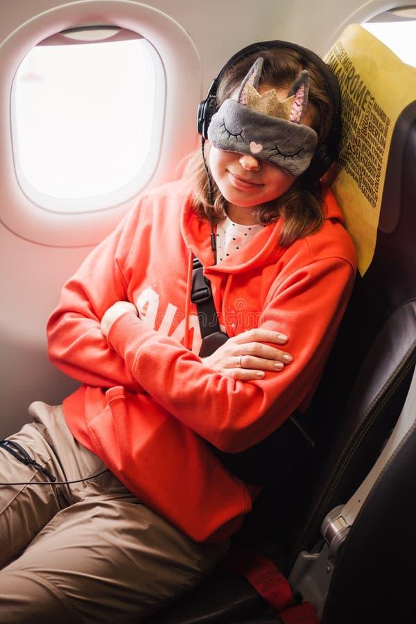 Donna che dorme in aeroplano mentre viaggiando immagini stock