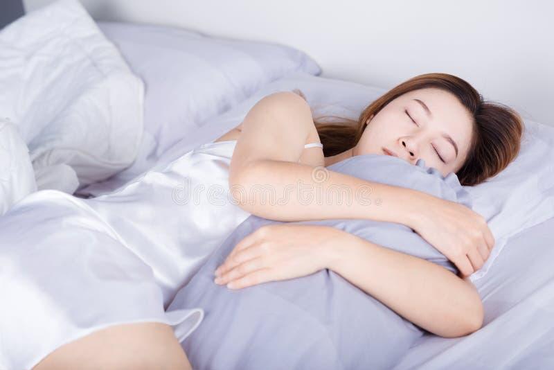 Donna che dorme con il cuscino del sostegno sul letto in camera da letto immagine stock