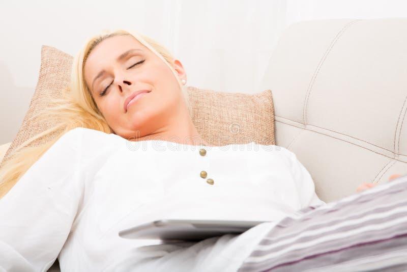 Donna che dorme con la compressa sul sofà fotografia stock libera da diritti
