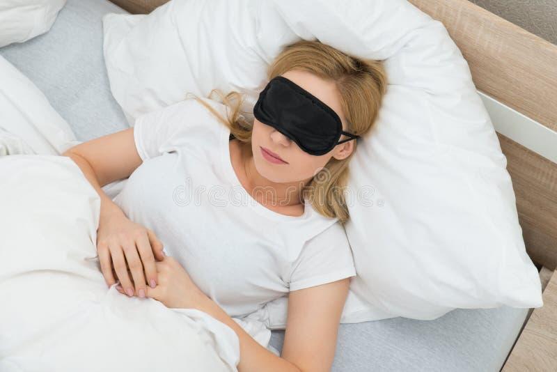 Donna che dorme con la maschera di sonno fotografia stock libera da diritti