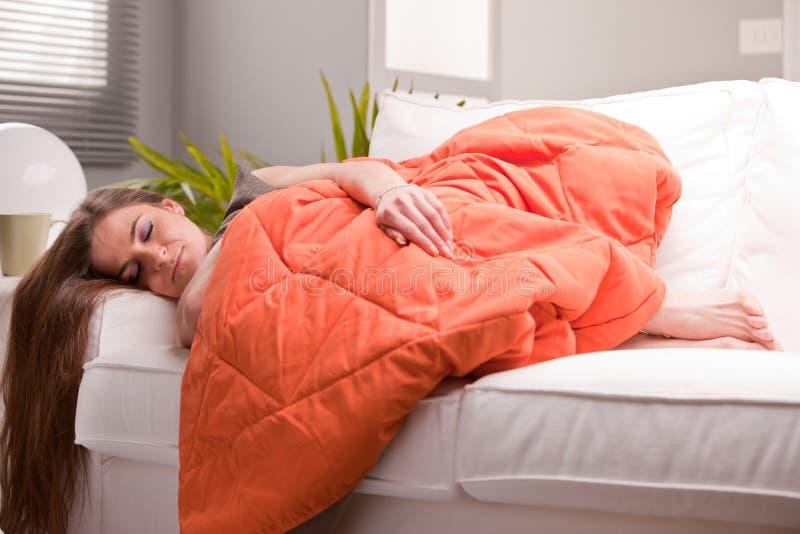 Donna che dorme morbidamente sul suo sofà fotografia stock libera da diritti