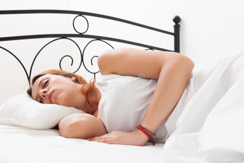 Donna che dorme pacificamente nel suo letto a casa fotografie stock libere da diritti
