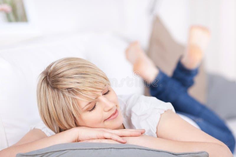 Donna che dorme su un sofà fotografia stock