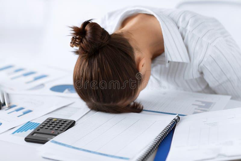 Donna che dorme sul lavoro nella posa divertente fotografia stock libera da diritti