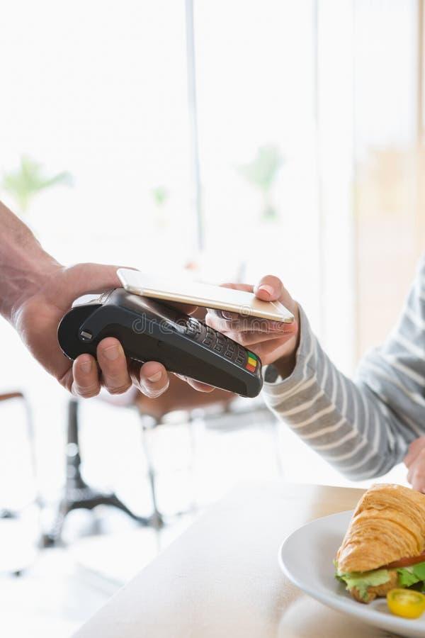 Donna che effettua pagamento con NFC immagini stock libere da diritti
