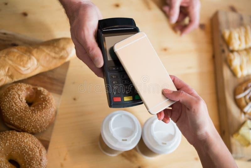 Donna che effettua pagamento con NFC fotografia stock libera da diritti