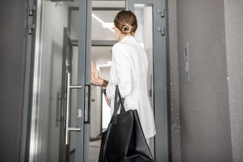 Donna che entra in edificio residenziale fotografia stock