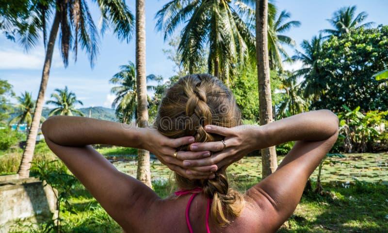 Donna che esamina bella vista tropicale con le palme ed il piccolo stagno fotografie stock libere da diritti