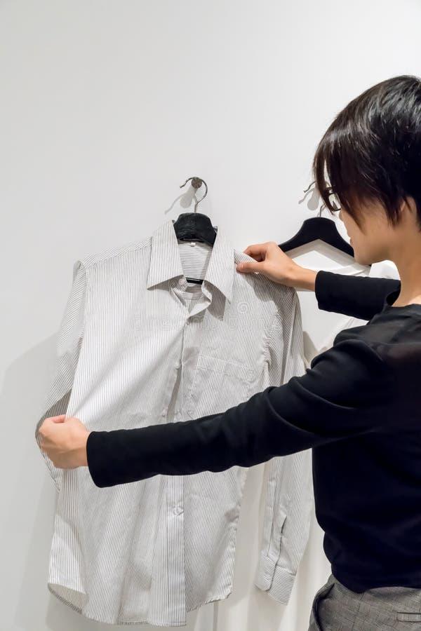 Donna che esamina camicia a strisce fotografia stock