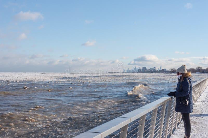 donna che esamina ghiaccio sul lago Michigan con l'orizzonte di Chicago nel fondo immagini stock