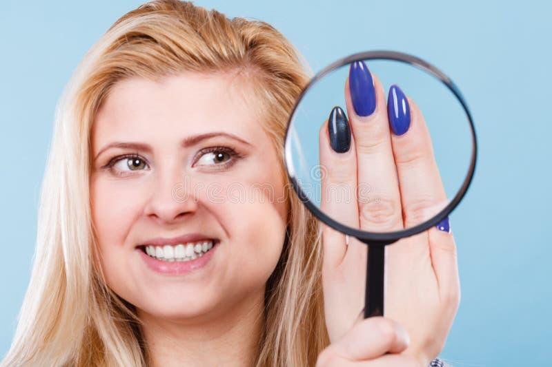 Donna che esamina i chiodi tramite la lente d'ingrandimento fotografie stock libere da diritti
