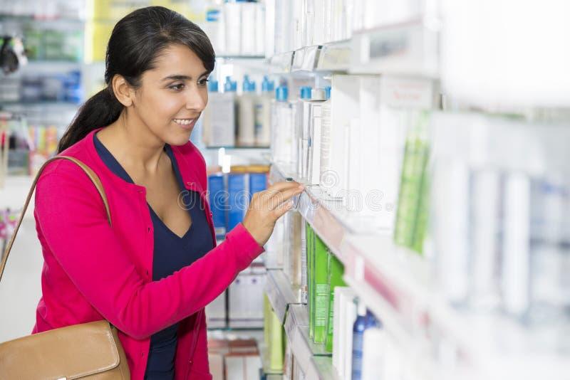 Donna che esamina i cosmetici sullo scaffale in farmacia fotografia stock