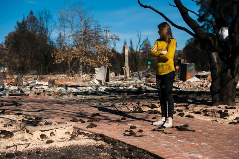 Donna che esamina la sua casa bruciata dopo il disastro del fuoco immagini stock libere da diritti