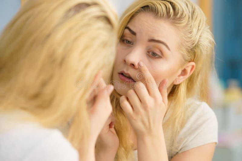 Donna che esamina la sua pelle in specchio fotografie stock libere da diritti