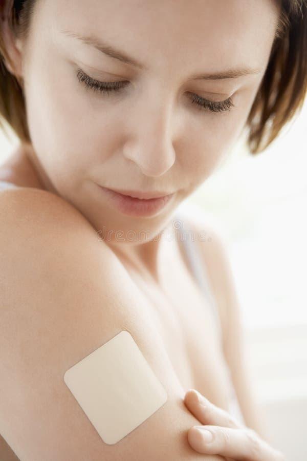 Donna che esamina la toppa del nicotina sul braccio immagine stock libera da diritti