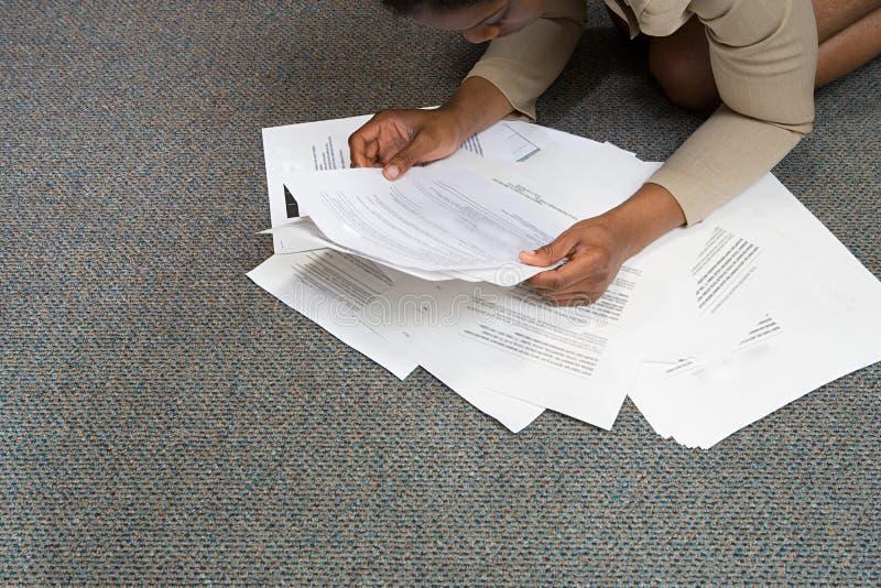 Donna che esamina lavoro di ufficio sul pavimento fotografia stock