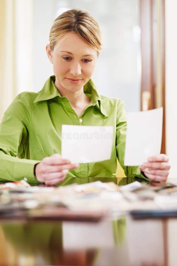 Donna che esamina le foto fotografie stock