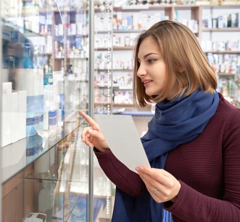 Donna che esamina lo scaffale della farmacia con i prodotti medici fotografie stock libere da diritti