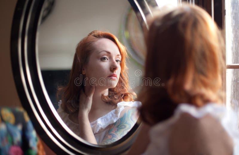 Donna che esamina lo specchio fotografie stock libere da diritti