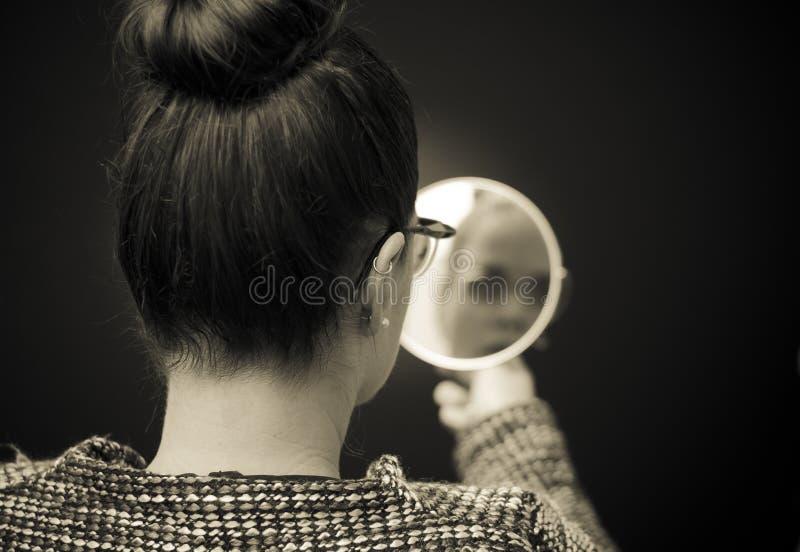 Donna che esamina riflessione di auto in specchio fotografia stock