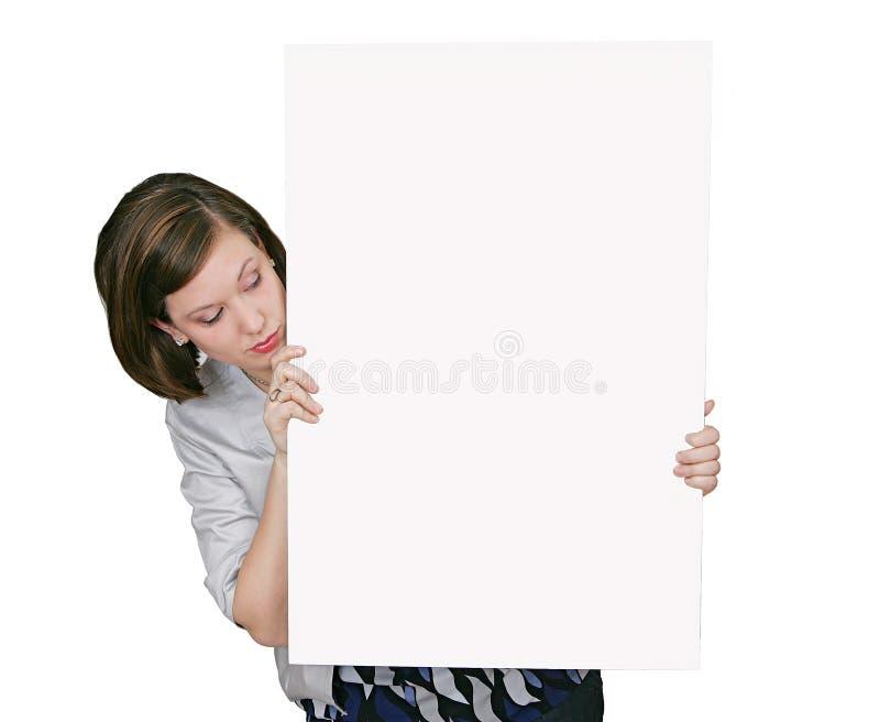 Donna che esamina segno in bianco immagine stock