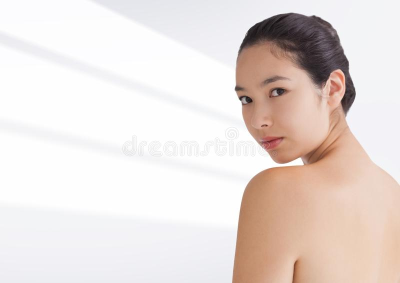 Donna che esamina spalla contro il fondo bianco immagini stock libere da diritti