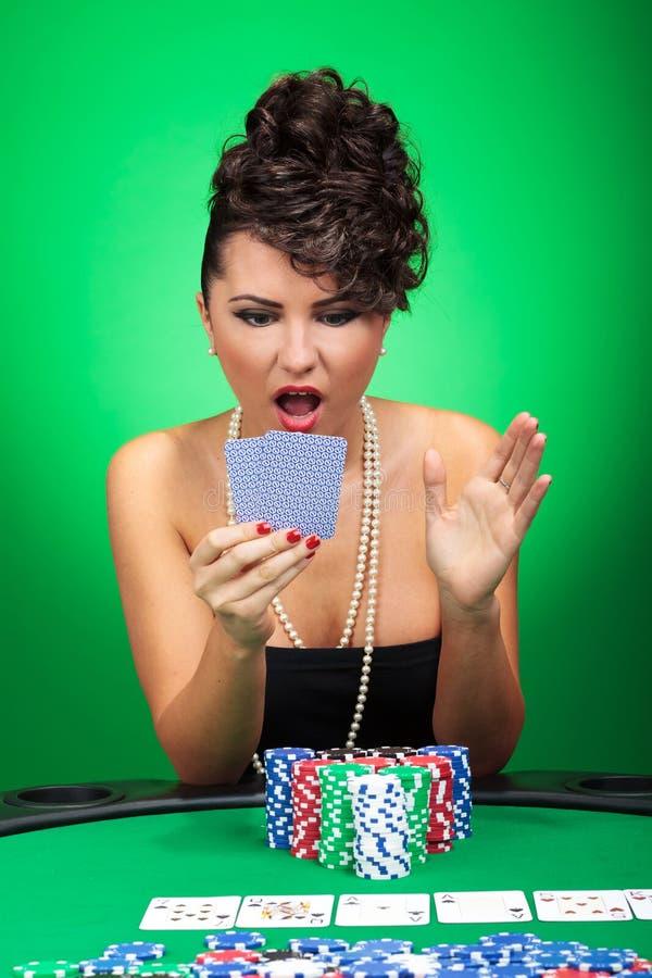 Donna che esamina stupita le schede fotografie stock libere da diritti