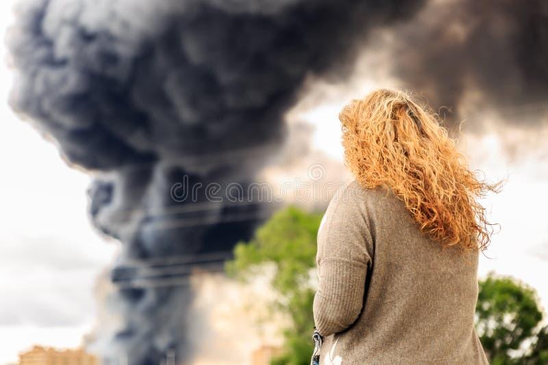 Donna che esamina un fumo enorme da un grande fuoco fotografie stock libere da diritti
