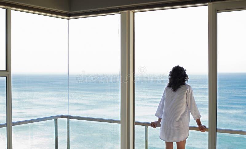 Donna che esamina vista del mare dal balcone fotografie stock