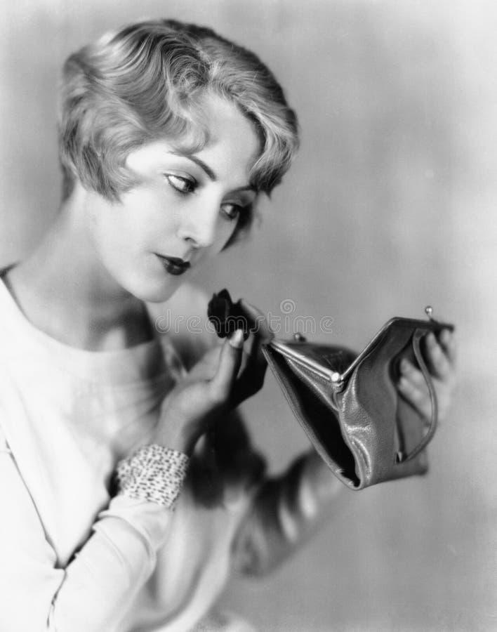Donna che esaminano uno specchio in sua borsa e stendere il trucco (tutte le persone rappresentate non sono vivente più lungo e n fotografia stock libera da diritti