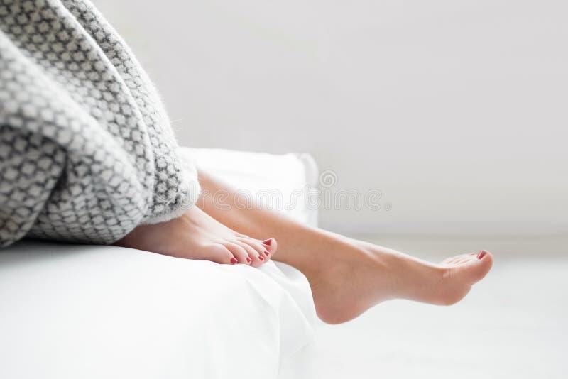 Donna che esce letto accogliente, in primo luogo punto sveglio immagine stock