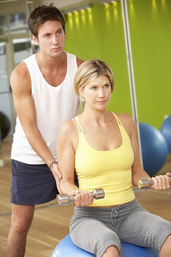 Donna che esercita incoraggiamento dall'istruttore personale In Gym fotografia stock libera da diritti