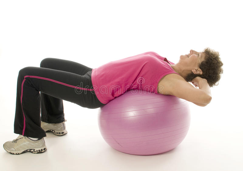 Donna che esercita la sfera di forma fisica di addestramento di memoria immagini stock