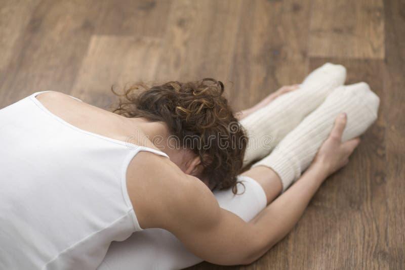 Donna che fa allungando esercizio sul pavimento di legno duro immagine stock