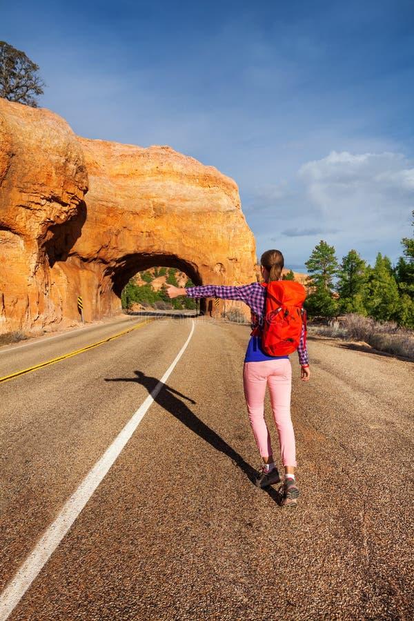 Donna che fa auto-stop sulla strada vicino al canyon rosso immagine stock