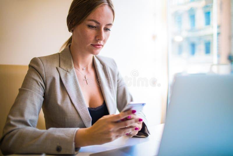Donna che fa deposito di compera online tramite telefono cellulare dopo la videoconferenza sul computer portatile immagini stock